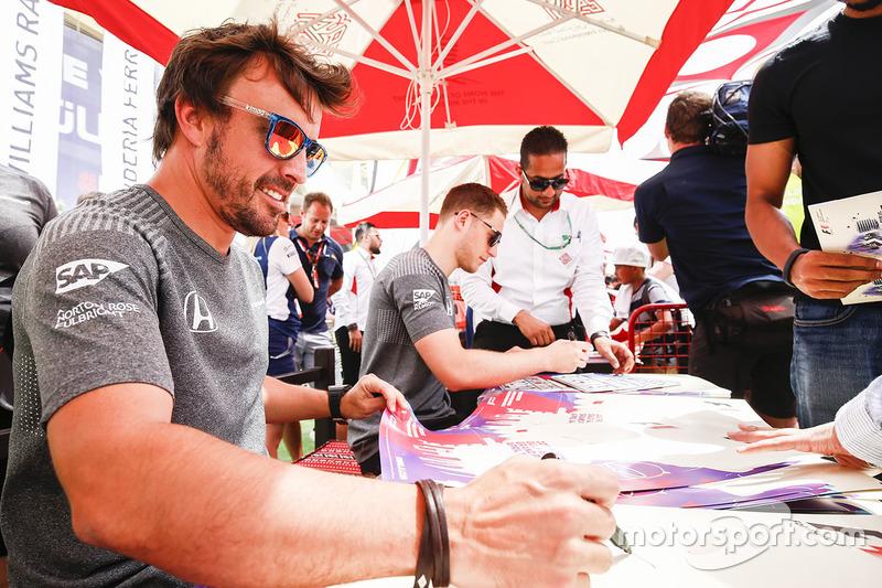 Fernando Alonso, McLaren, and Stoffel Vandoorne, McLaren, sign autographs for fans