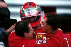 Il vincitore Michael Schumacher, Ferrari F310B e Jean Todt abbracciano Eddie Irvine, Ferrari F310B