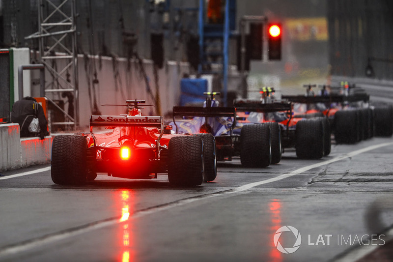 Cars queue to leave the pit lane