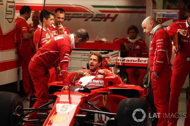 Sebastian Vettel, Ferrari, lowers himself into the cockpit of his car fitted with a new protective shield