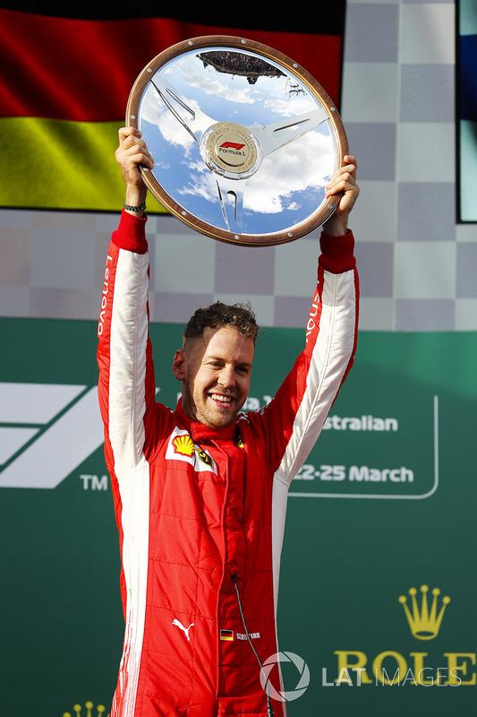 Sebastian Vettel, Ferrari, 1st position, lifts his trophy on the podium
