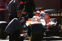 A Pirelli engineer checks a tyre on the Fernando Alonso McLaren MCL32