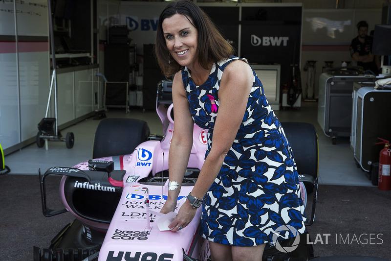 Lee McKenzie, presentadora de canal 4 F1 pone una pegatina de la Asociación de atención de cáncer de mama en el Force India F1