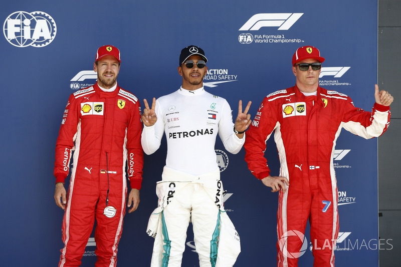 Sebastian Vettel, Ferrari, Polesetter Lewis Hamilton, Mercedes AMG F1, and Kimi Raikkonen, Ferrari, celebrate after qualifying