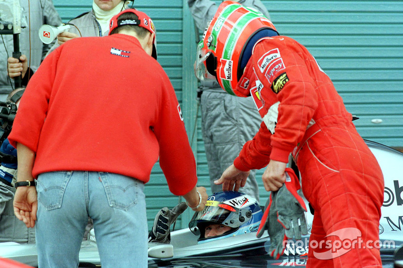 Ferrari drivers Michael Schumacher and Eddie Irvine congratulate the new Formula One World Champion Mika Hakkinen, McLaren