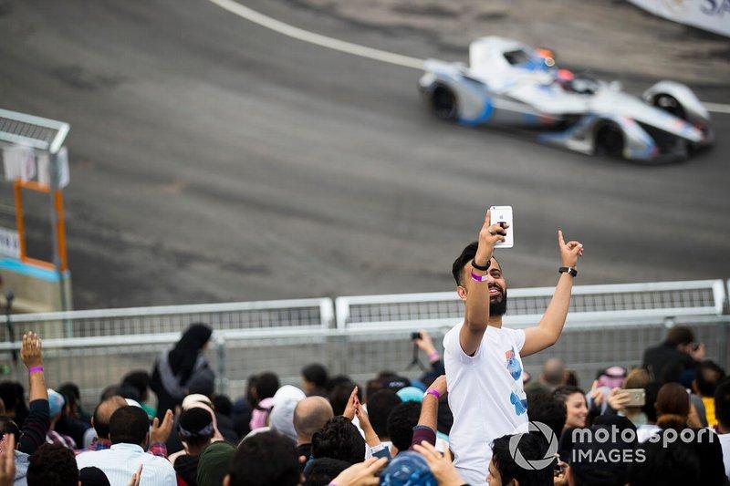 un fan scatta un selfie con una monoposto che transita alle sue spalle