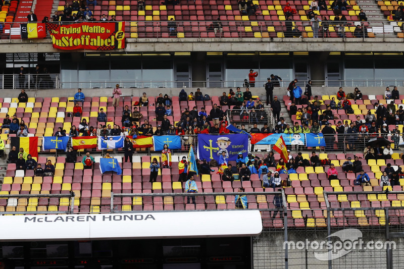 Fans in the pit straight grandstand wait during a weather delay in FP2