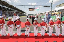 Niños de la parrilla dándose la mano con Chase Carey, dueño de Formula One y Sean Bratches, Director Gerente de Operaciones Comerciales, Formula One Group