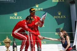 Race winner Sebastian Vettel, Ferrari, shakes hands with Nathalie McGoin on the podium