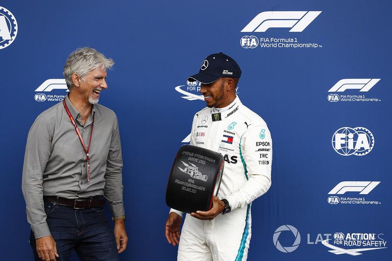 Damon Hill remet un trophée Pirelli à Lewis Hamilton après sa pole position