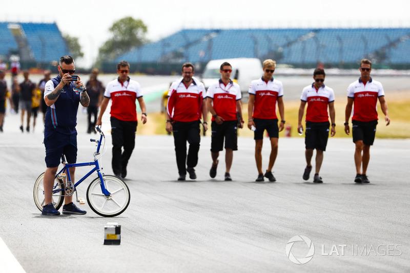 Un membro del team Williams, su una bici, scatta una foto
