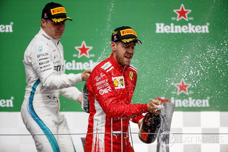 Valtteri Bottas, Mercedes AMG F1, 2nd position, and Sebastian Vettel, Ferrari, 1st position, celebrate with Champagne