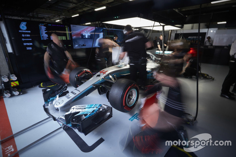 Mercedes engineers work on the car of Lewis Hamilton, Mercedes AMG F1 W08, in the garage