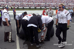 Dale Jarrett climbs out of his wrecked UPS Ford Taurus as the crew survey the damage