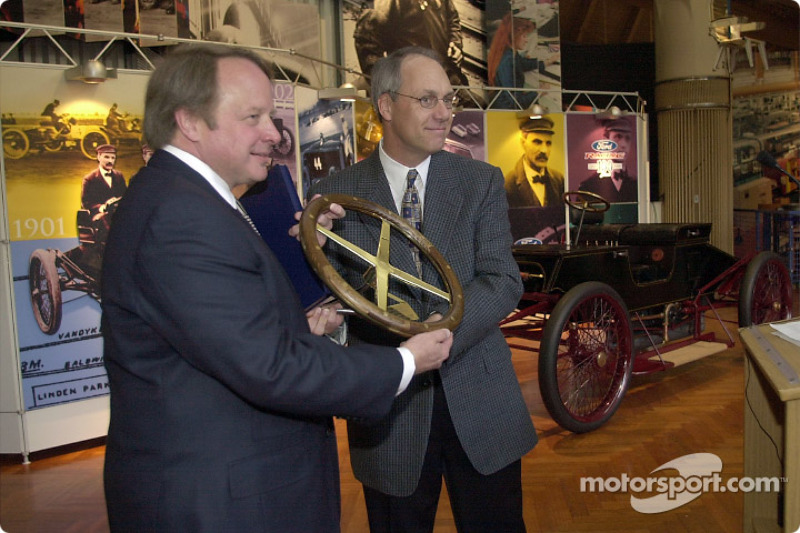 Dan Davis Director of Ford Racing Technologies, presents a commemorative steering wheel to Edsel B. Ford II, during a ceremony to unveil a restored Ford 1901 Sweepstakes at the Henry Ford Museum