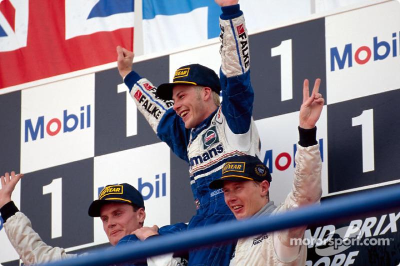 Le podium: le Champion du Monde Jacques Villeneuve avec David Coulthard et Mika Hakkinen