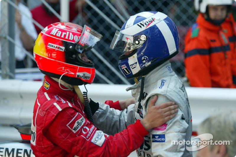 Michael Schumacher felicitaando al ganador de la carrera, David Coulthard