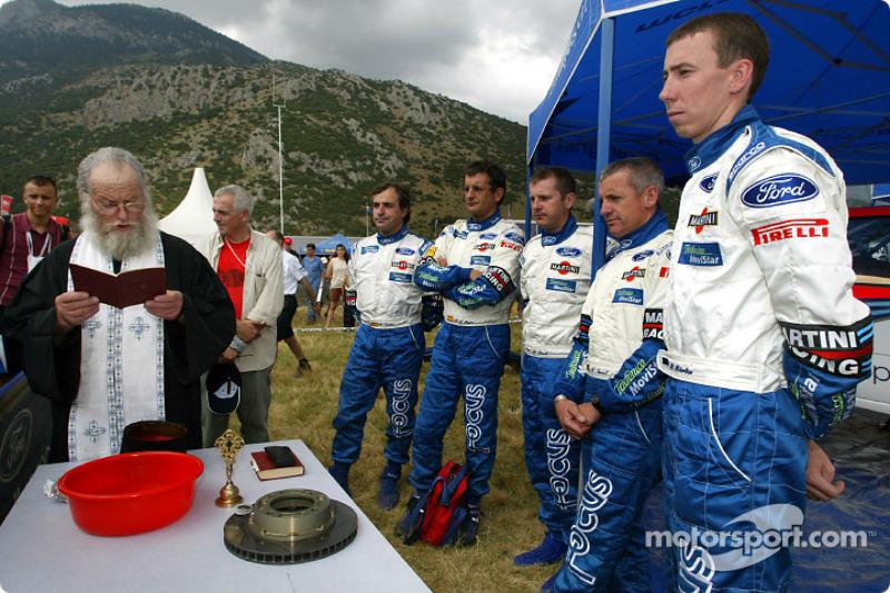 Pilotos de Ford recibiendo la bendición de un sacerdote Griego Ortodoxo