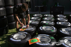 McLaren team members prepare the tires