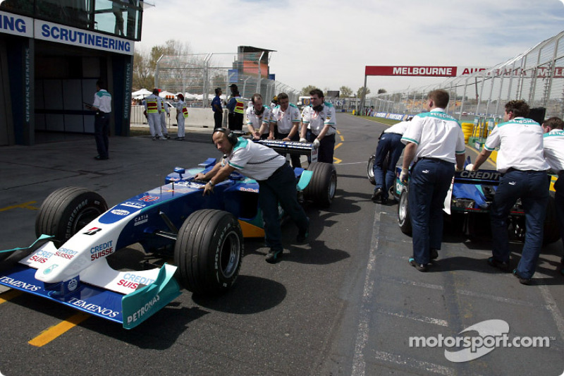 Sauber crew members push the cars to the Parc Fermé