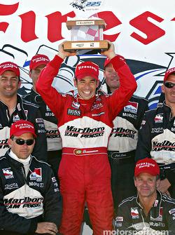 Race winner Helio Castroneves celebrates with his team