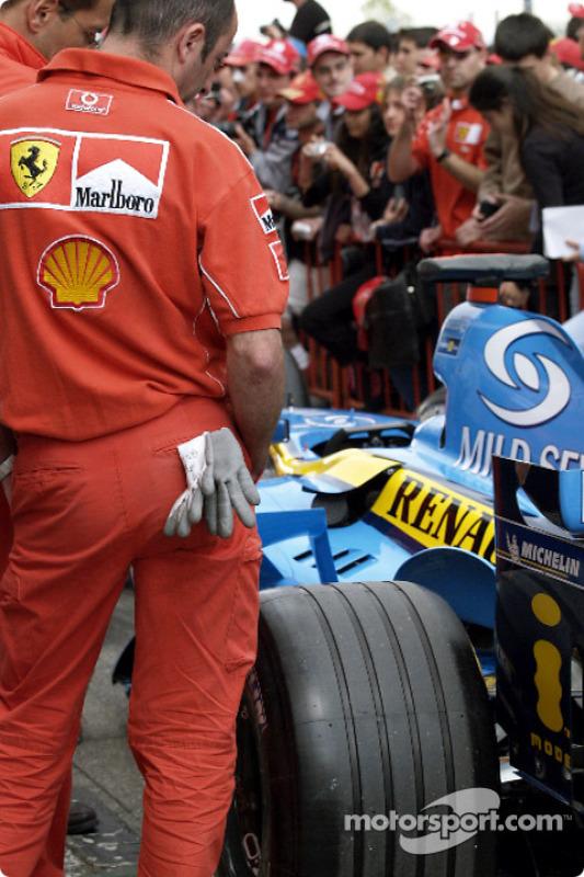Des membres de l'équipe Ferrari inspectent la Renault F1