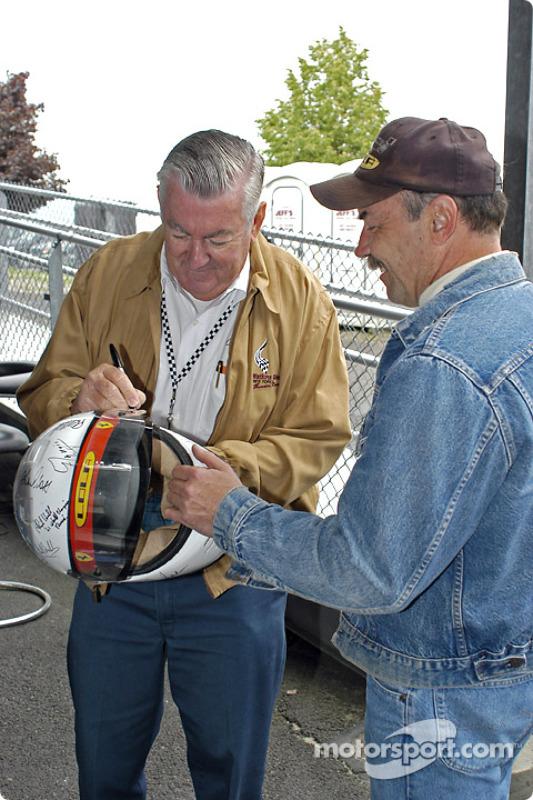 Bobby Allison autographs a helmet