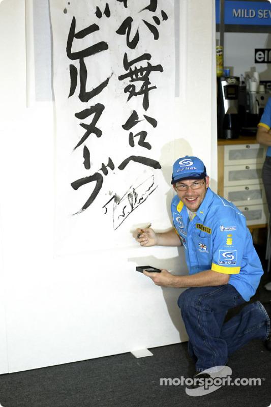 Jacques Villeneuve signe un autographe sur une bannière