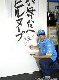 Jacques Villeneuve signs his autograph on a banner