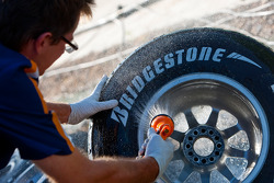 A Trident Racing mechanic washes a tyre