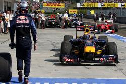 Sebastian Vettel, Red Bull Racing walks out of parc ferme as Mark Webber, Red Bull Racing the winner drives in