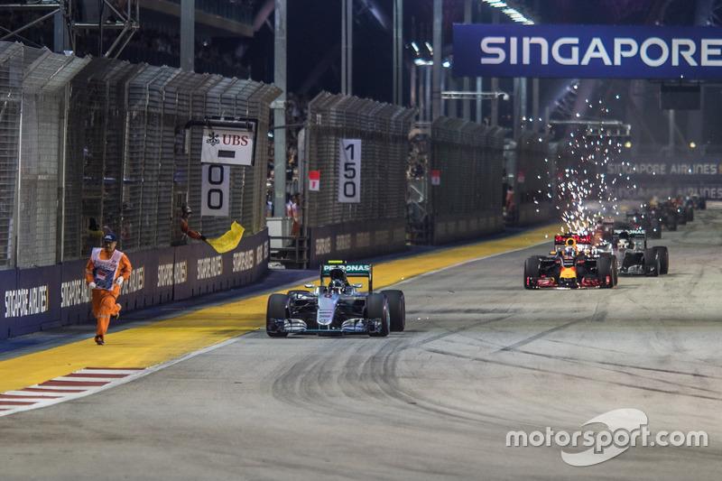 Un oficial de pista corre por el circuito frente a Nico Rosberg