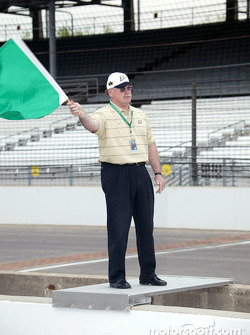 Joe Tiller, head football coach for Purdue University, waves green flag