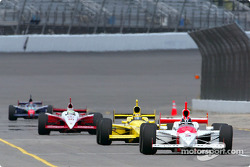 Helio Castroneves leads a group of cars on pitlane