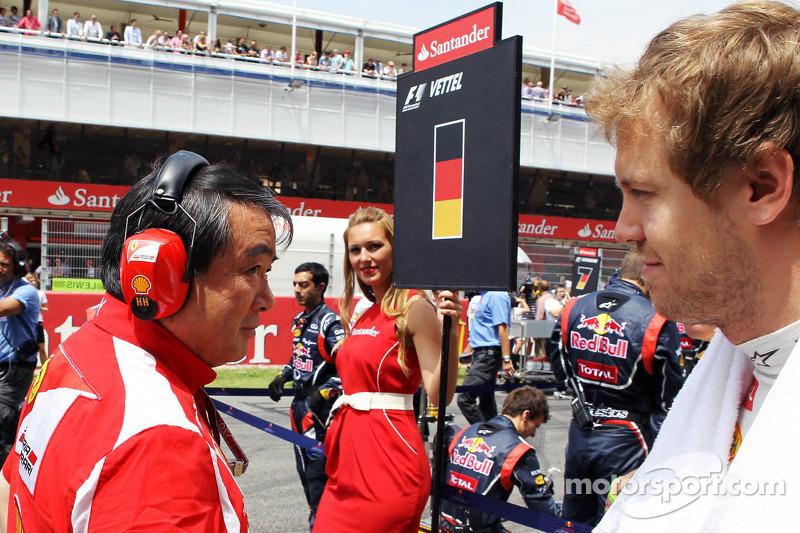 Sebastian Vettel, Red Bull Racing passeert Hirohide Hamashima, Scuderia Ferrari Tyre Engineer op de grid