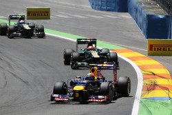 Mark Webber, Red Bull Racing leads Heikki Kovalainen, Caterham and Vitaly Petrov, Caterham