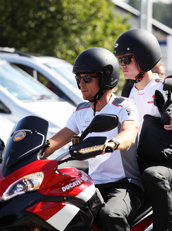 Jenson Button, McLaren arrrives at the circuit on a motorbike with Mike Collier, Personal Trainer