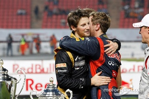 Romain Grosjean is greeted by Sebastian Vettel