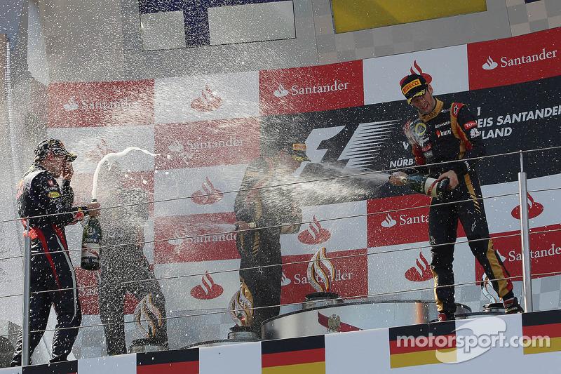 (L naar R): racewinnaar Sebastian Vettel, Red Bull Racing viert feest op het podium met Kimi Raikkon