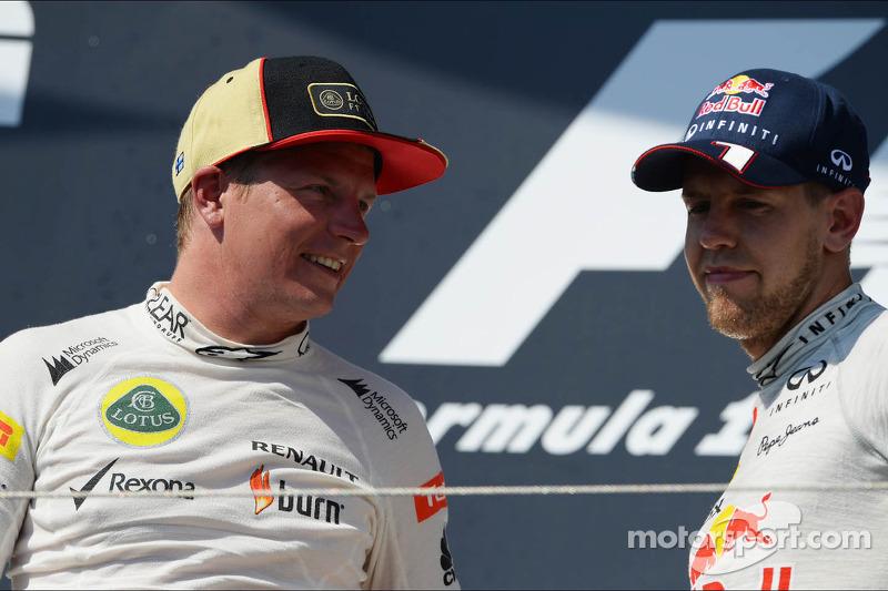 (L naar R): de als tweede gefinishte Kimi Raikkonen, Lotus F1 Team met de als derde geklasseerde Sebastian Vettel, Red Bull Racing op het podium