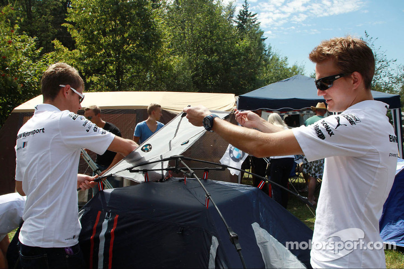 BMW-coureurs helpen met het bouwen van de tenten voor fans