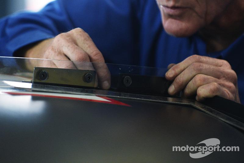 Een teamlid checkt een aerodynamisch apparaat op het dak van de auto