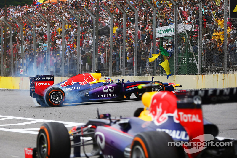 Race winner Sebastian Vettel, Red Bull Racing RB9 celebrates at the end of the race with donuts as Mark Webber, Red Bull Racing RB9 passes, without his helmet