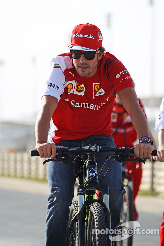Fernando Alonso, Ferrari on his bicycle rides the perimeter road around the circuit