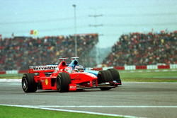 Eddie Irvine, Ferrari, is passed by Alexander Wurz, Benetton
