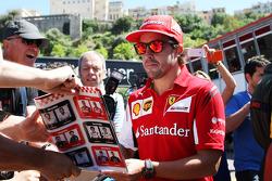 法拉利车队的费尔南多·阿隆索为车迷签名