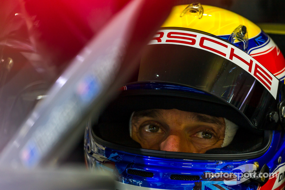 Mark Webber sitting in the car while it is inspected in the garage late in the race