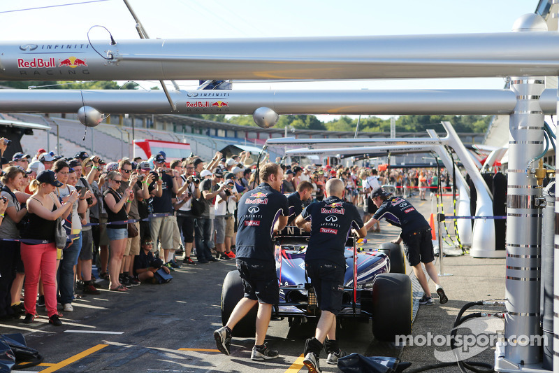 Fans in the pits watch the Red Bull Racing RB10 pushed down the pit lane