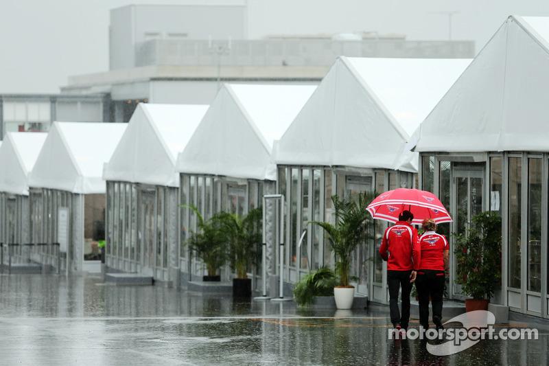 玛鲁西亚F1车队的朱尔斯·比安奇和玛鲁西亚F1车队推广主管特拉西·诺瓦克在湿润多雨的围场