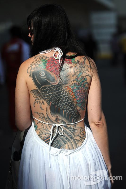 Mulher, com tatuagem de um peixe em seu pescoço